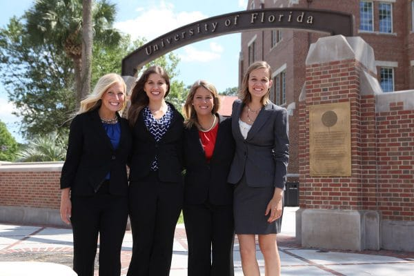 Four students pose in front of UF Warrington campus gateway