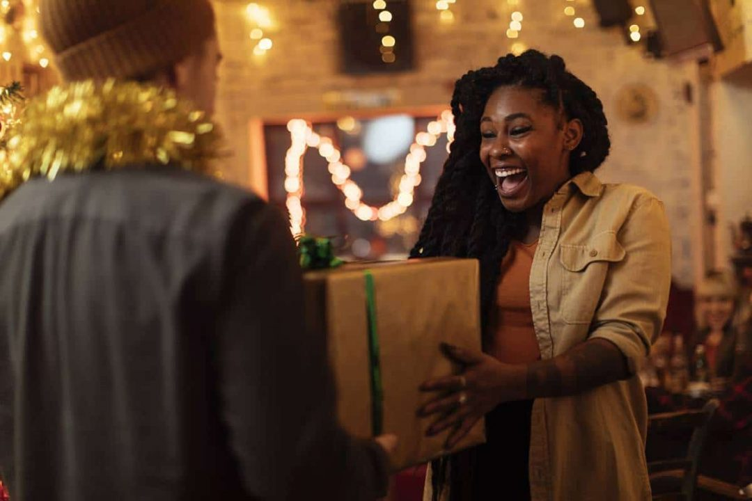 Boyfriend giving a Christmas present to his happy girlfriend