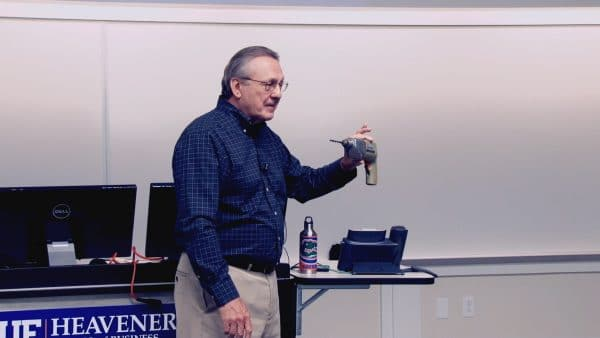 Richard Lutz holds a drill in the front of a classroom
