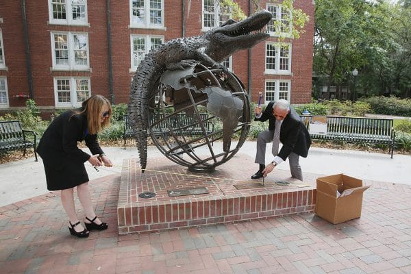 College of Law Dean Laura A. Rosenbury and College of Business Dean John Kraft pretend to be moving to each other's campus by the Gator Ubiquity Statue
