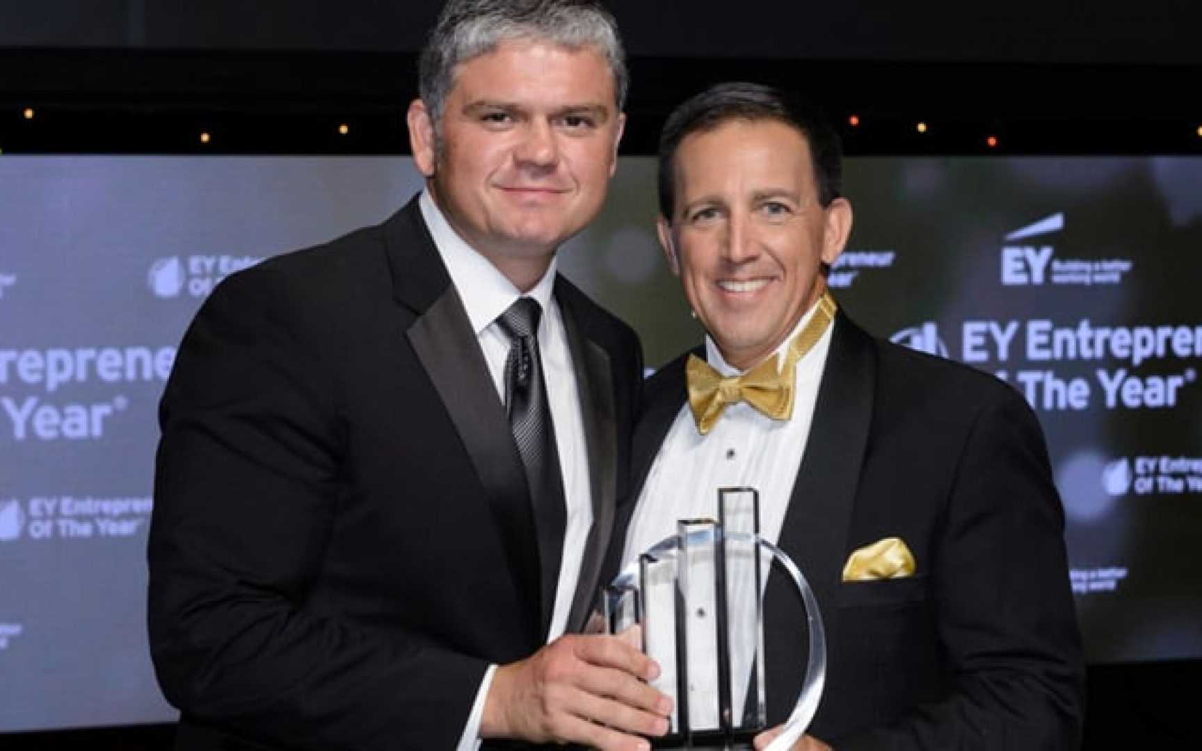 Nick Reader standing with another man accepting an award