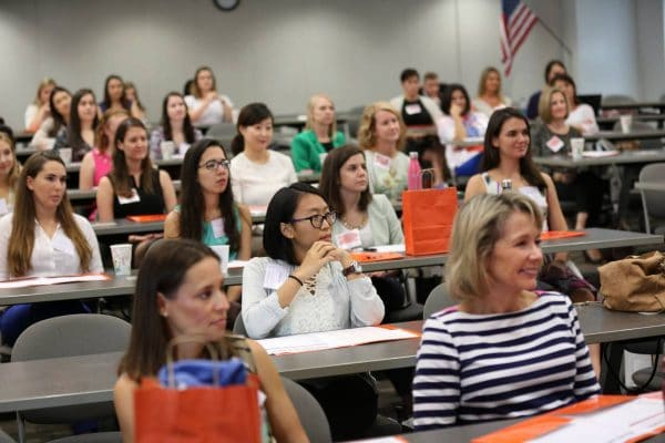 Large group of women sit in a classroom at the Women in Accounting Symposium