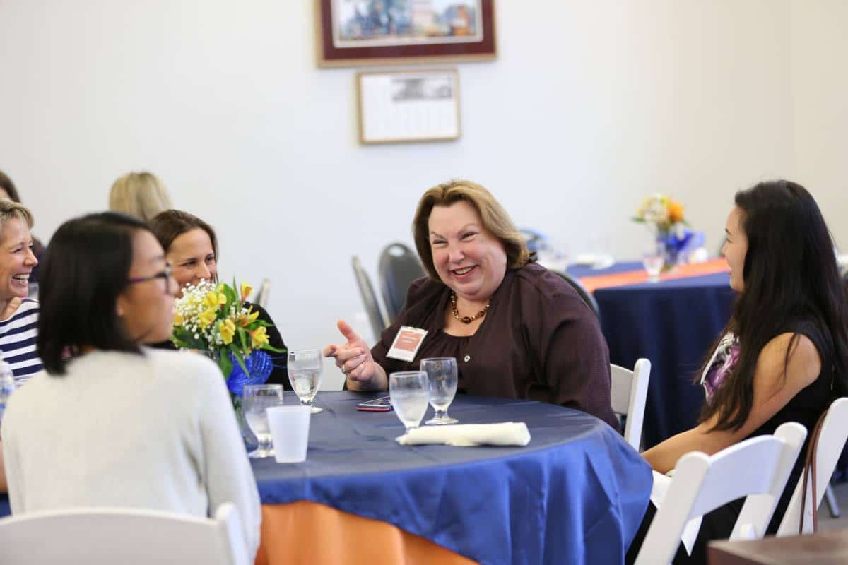 Barbara Jean Raskin seated at a table with students at the 11th Annual Women in Accounting Symposium