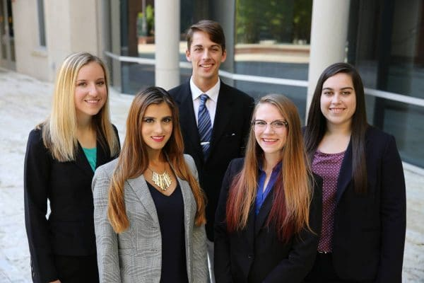 Five student members of Beta Alpha Psi pose in front of Hough Hall