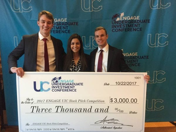 Three finance students hold a large check for $3,000 from a stock pitch competition