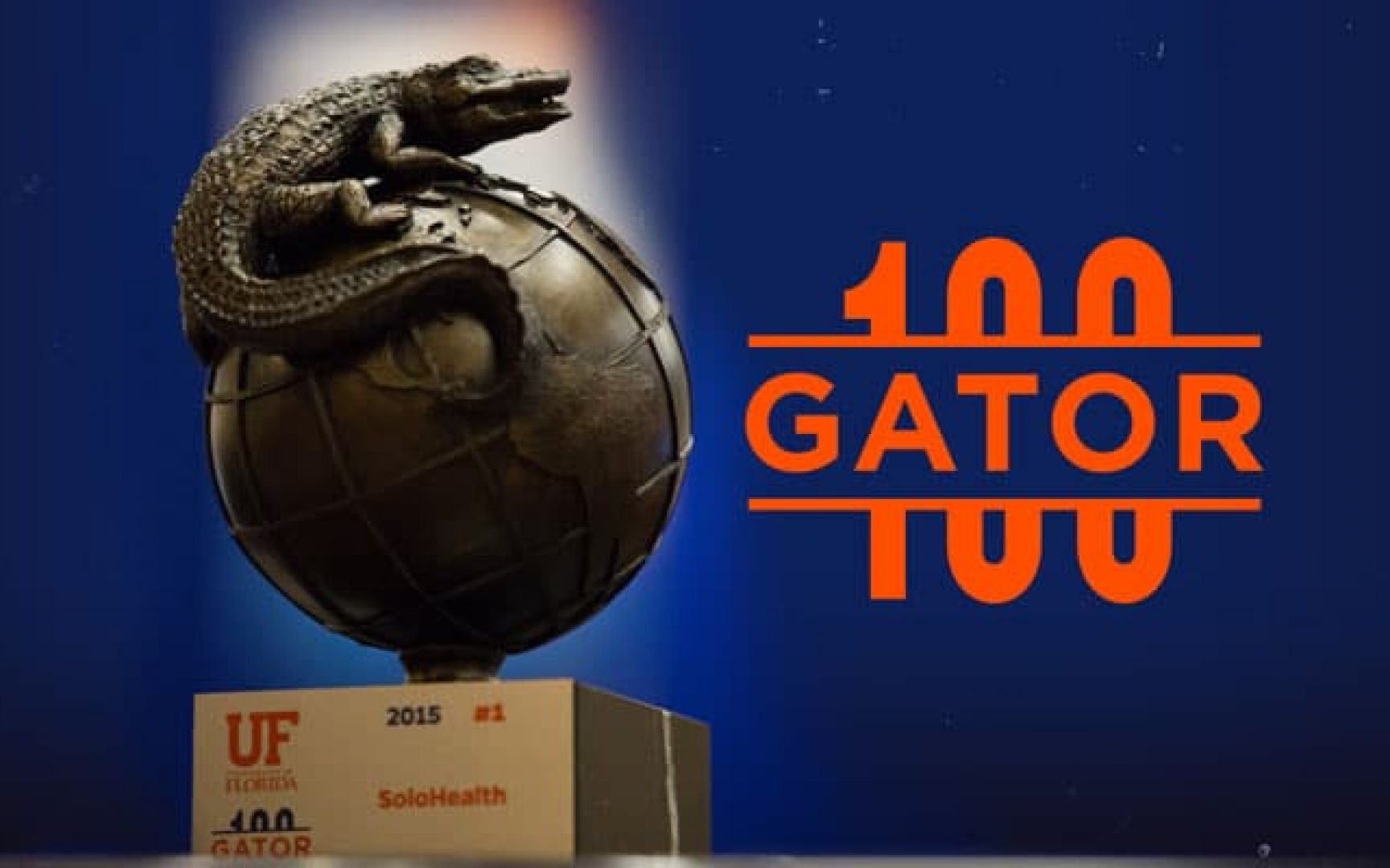 Gator 100 trophy next to the Gator 100 logo