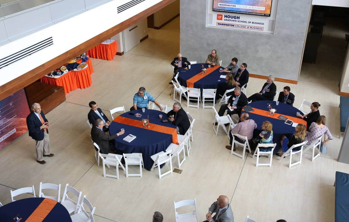 Dean John Kraft speaking at the Warrington Campaign Kickoff Showcase in the North Court of Hough Hall with people seated at round tables