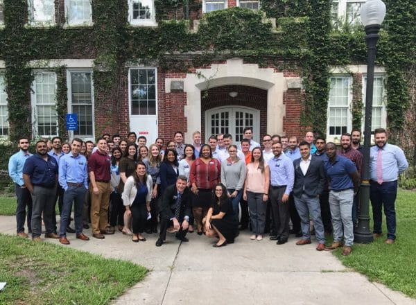 Large group of UF MBA students stand in front of Bryan Hall