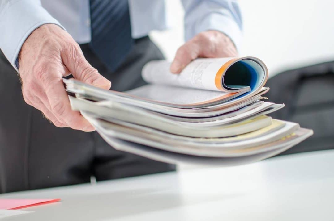 A man holding a stack of publications with the top one open