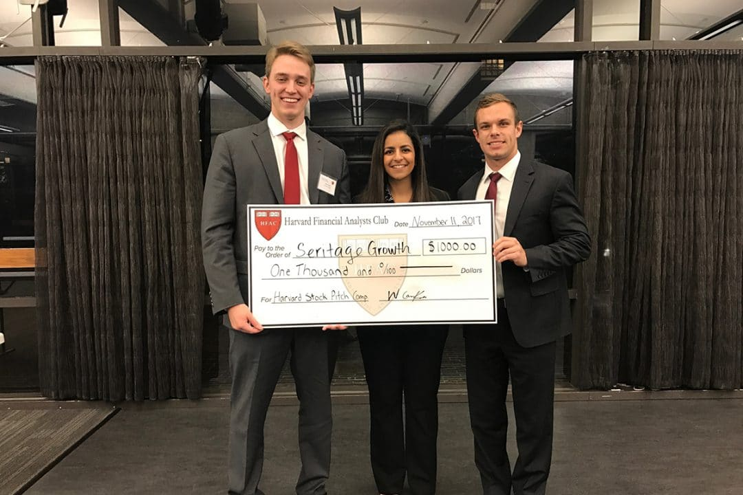 Three finance students hold a large check from their win at a Harvard Case Competition