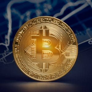 A bitcoin depicted as a real gold coin with a line graph blurred out in the background