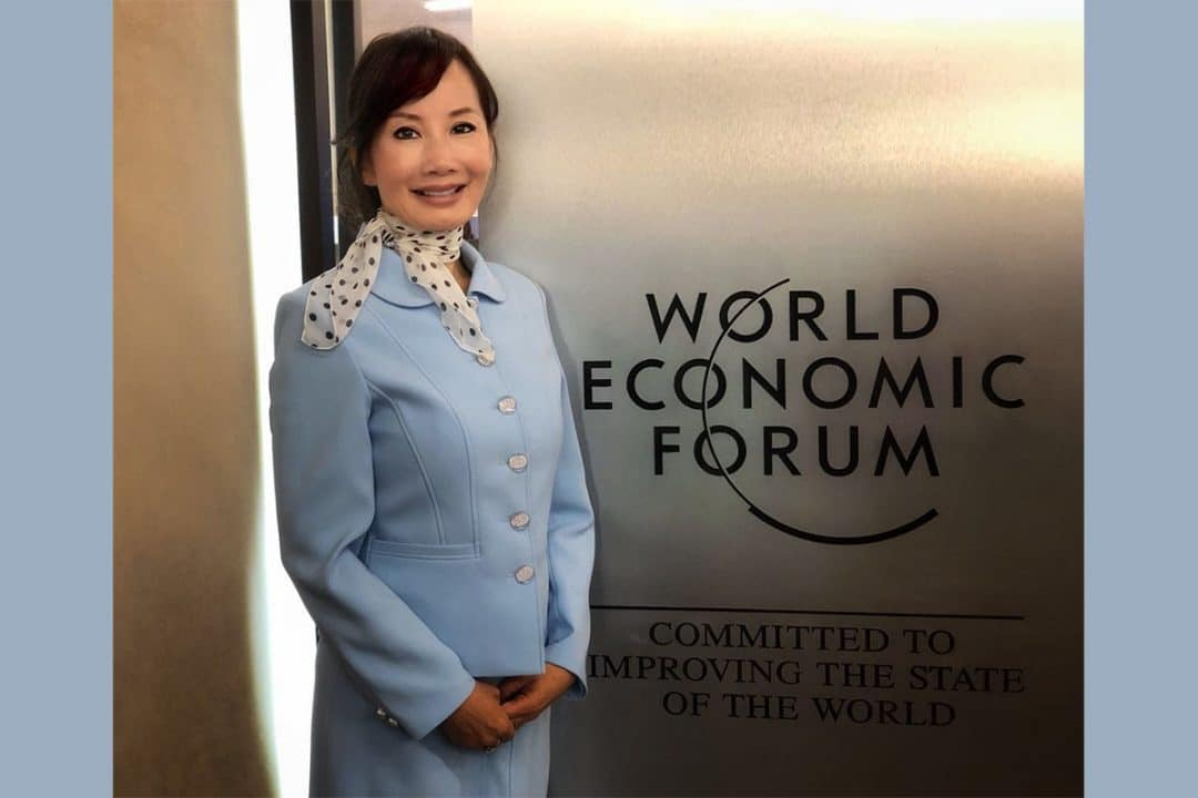 Jane Sun poses in front of a World Economic Forum sign