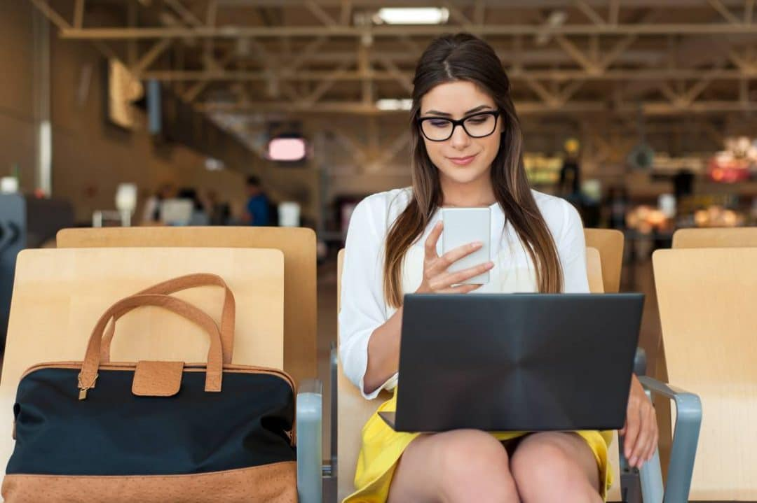 A woman sits in a chair looking at a smartphone with a laptop on her lap in a public indoor setting
