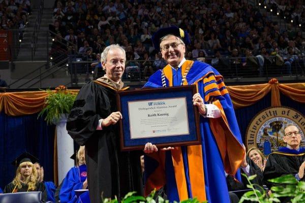 UF President Kent Fuchs hands Keith Koenig a framed distinguished alumnus award at commencement