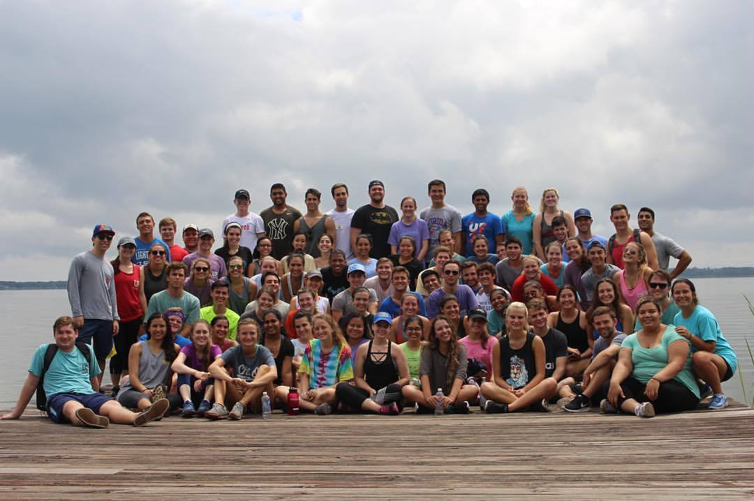 Large group of student members of the Heavener Leadership Challenge pose for a photo on a dock by a lake