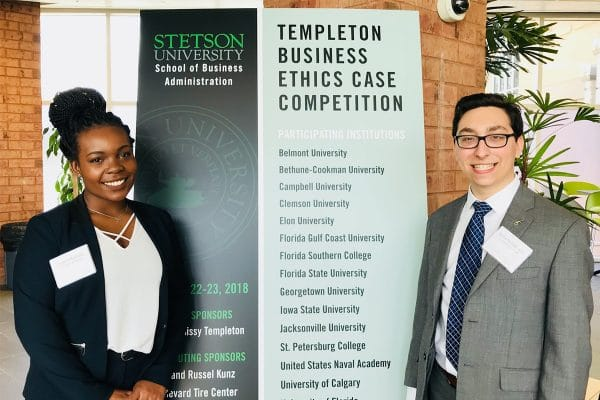 Crystal McDuffy & Justin Schlakman post with a sign for the Templeton Business Ethics Case Competition
