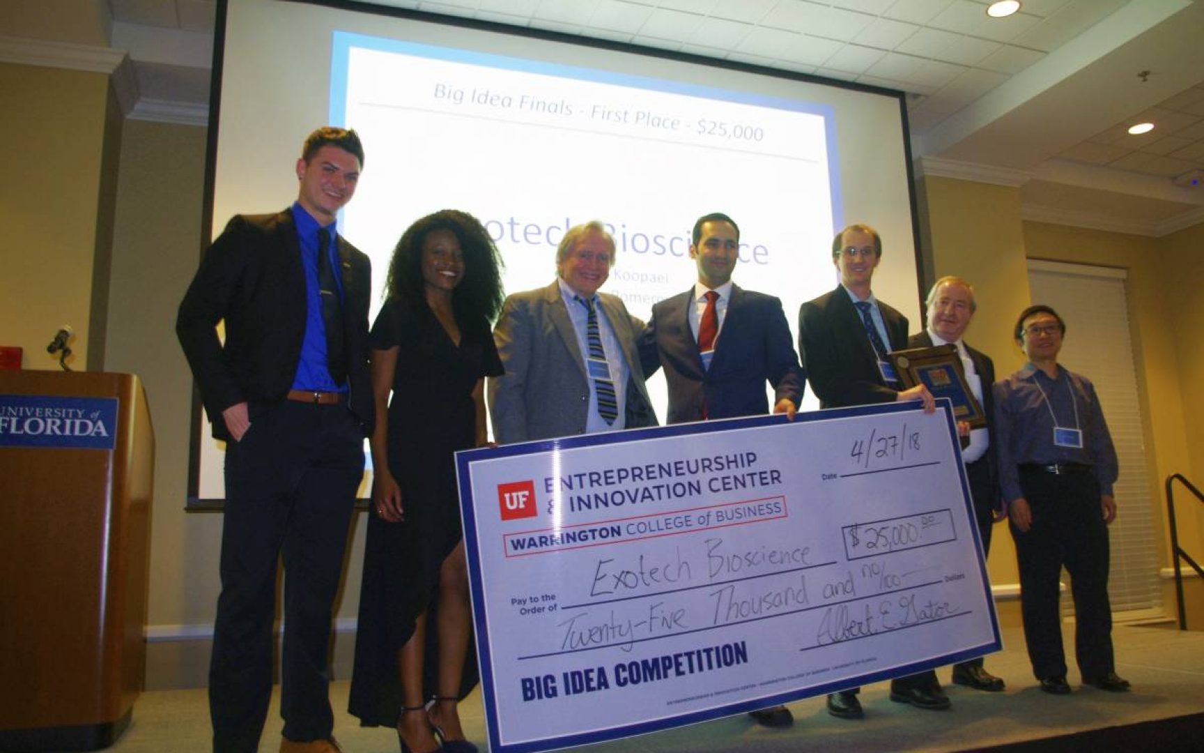 Group of students and faculty stand with a large check at the Big Idea Competition