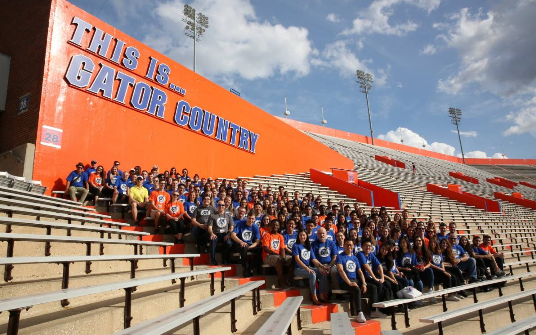 Large group of students sit in the UF Football stadium under a sign that reads This is Gator Country