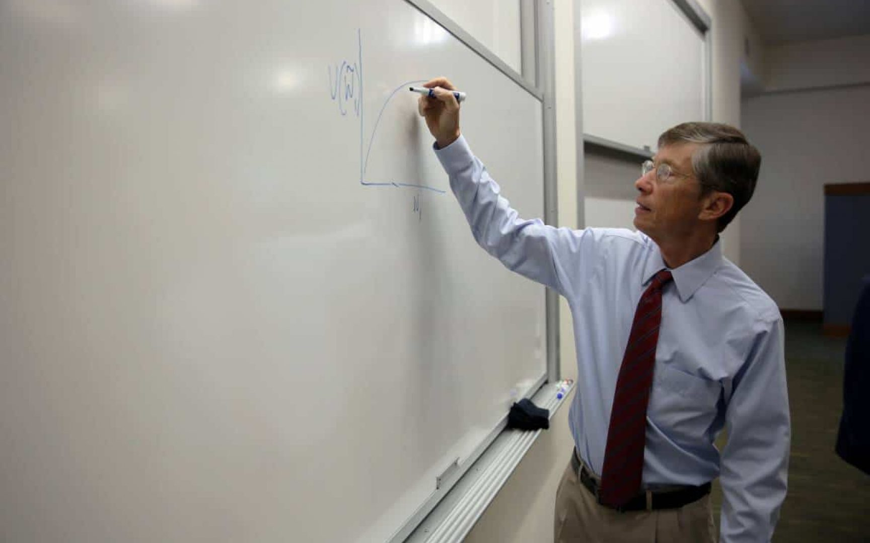 Jay Ritter draws a graph on a whiteboard in a classroom