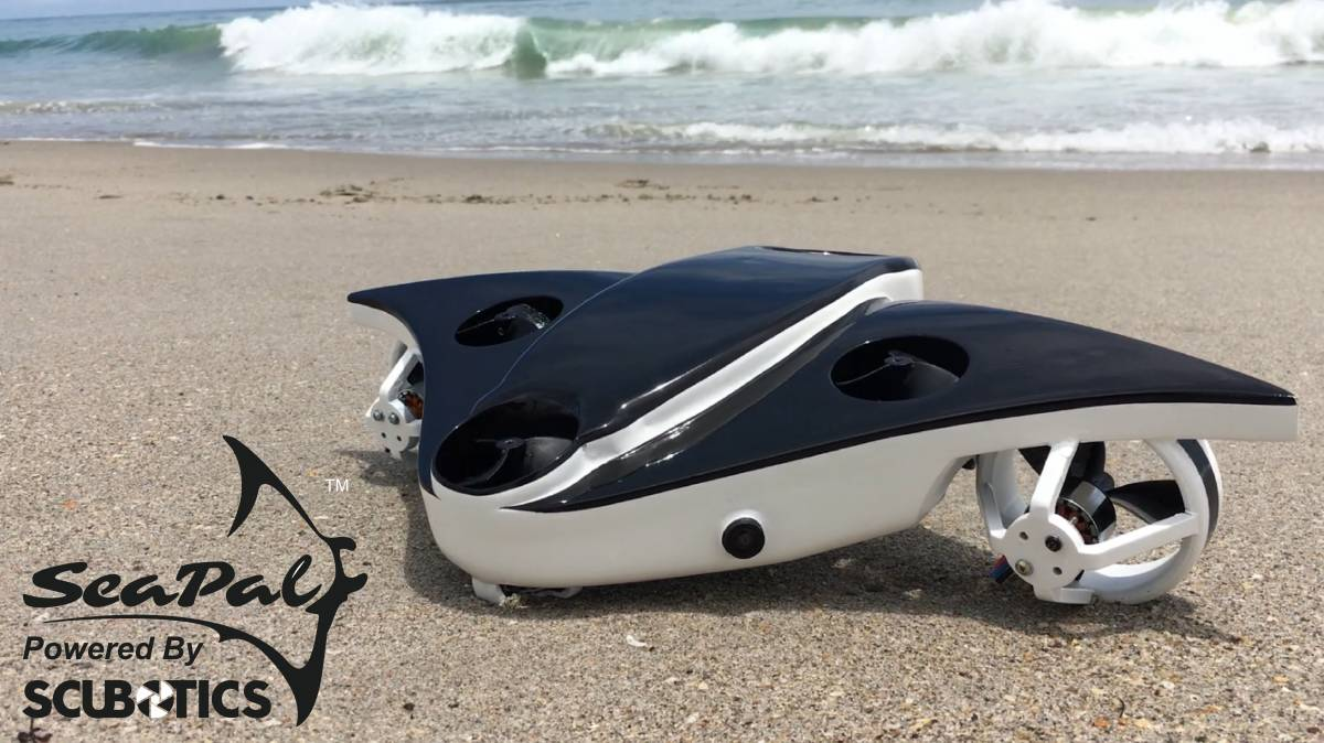 SeaPal, powered by SCUBOTICS, the underwater drone is pictured on a sandy beach with waves in the background