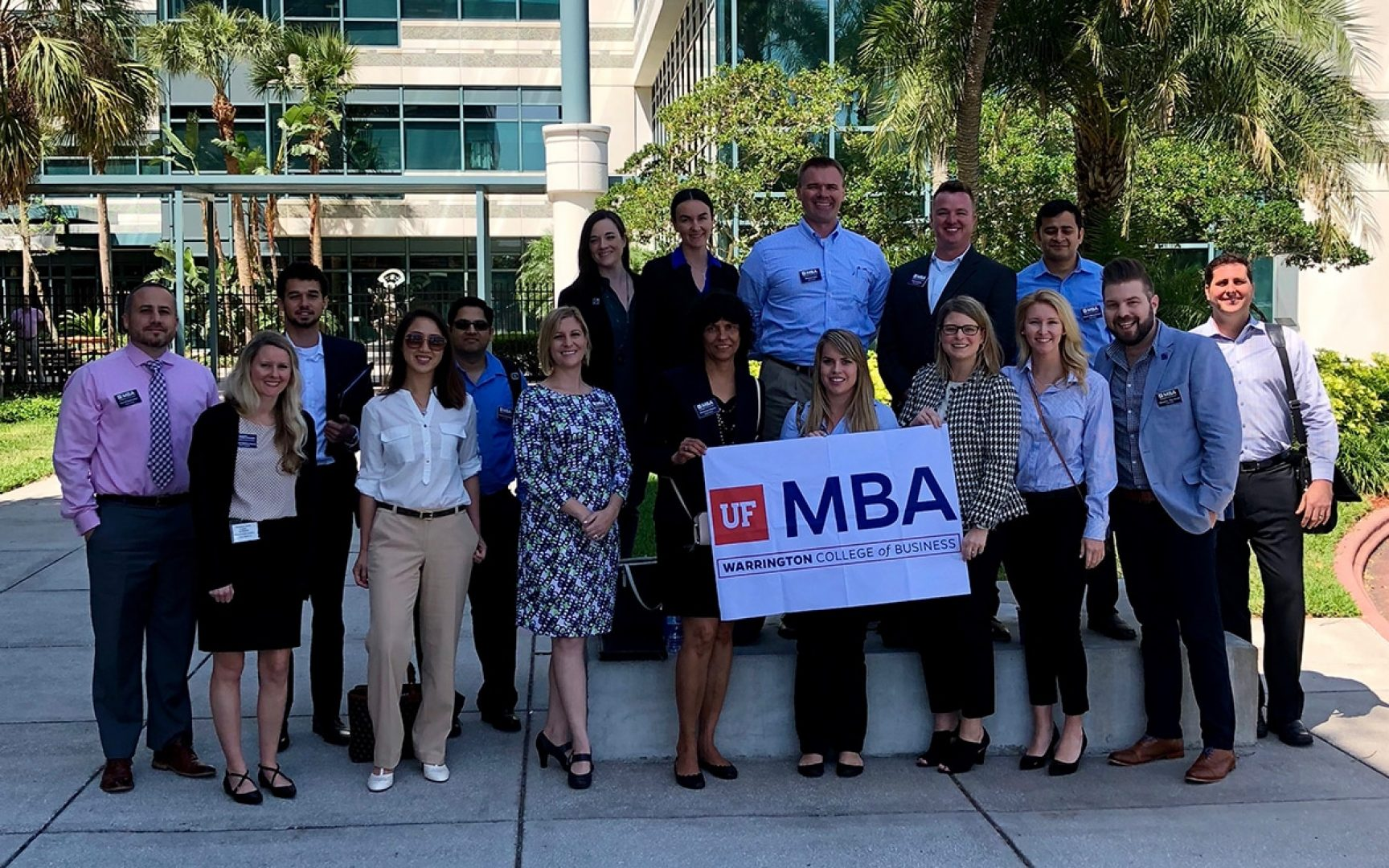 Students and staff from the UF MBA program pose for a photo outside of the Raymond James offices while holding a UF MBA banner