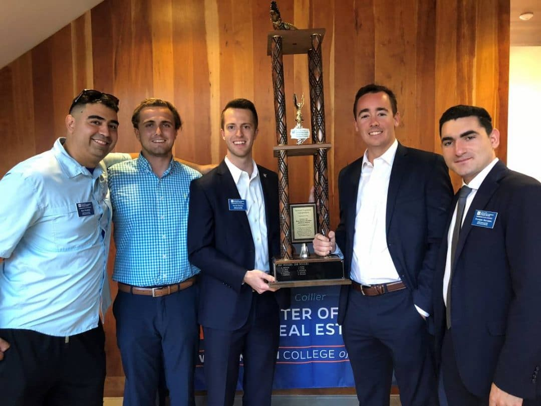Five male real estate students hold a trophy