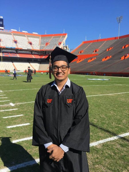 Sanjay Boodhoo stands on the football field in his graduation cap and gown