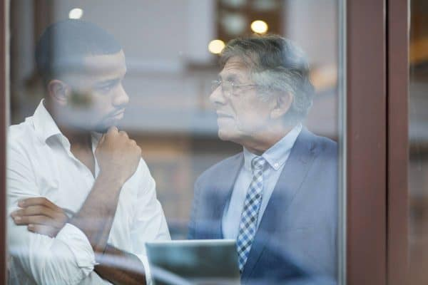 View through a window of two men, one young and one older, talking