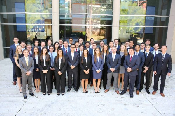 Large group of students in the Gator Student Investment Fund pose for a photo in front of Hough Hall
