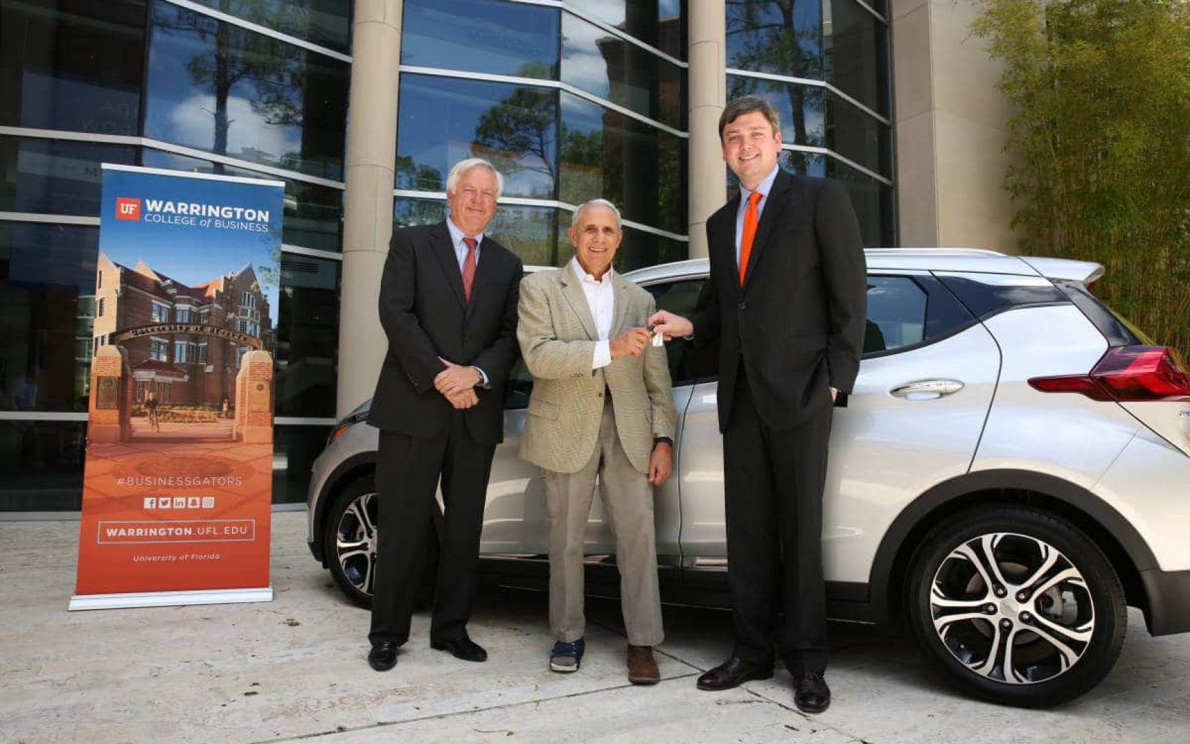 Three men stand in front of a car, and one man is handing keys to the car to another man