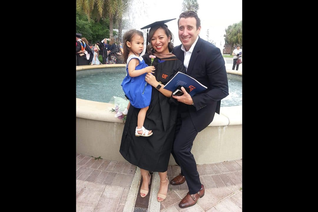 London Tawfik in a grad cap and gown pose with her daughter and husband