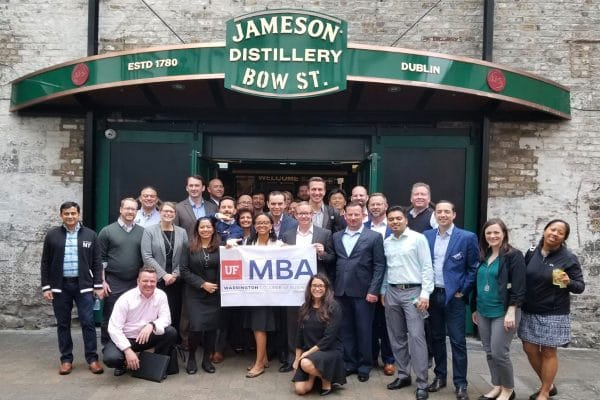 UF MBA students stand in front of the Jameson Distillery in Dublin holding a UF MBA banner