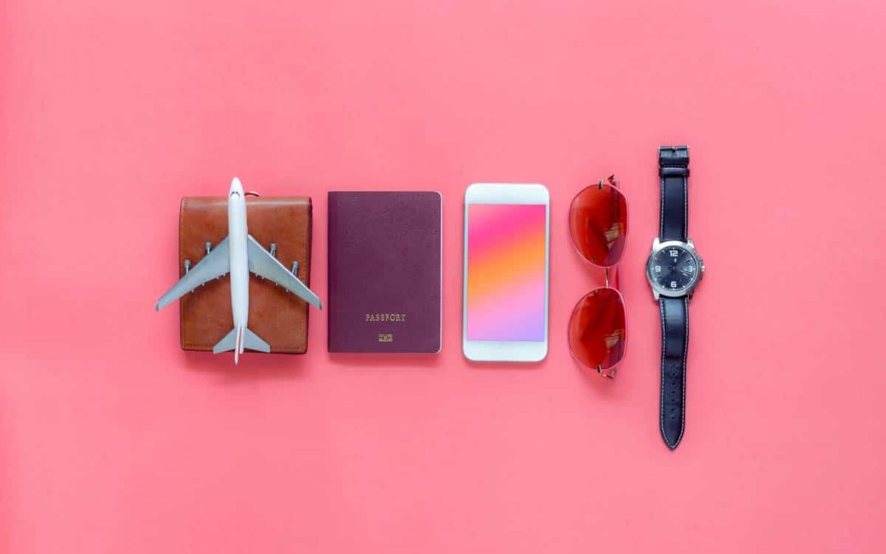 Pink background with small items including a toy airplane on a wallet, passport, iPhone, sunglasses and a watch