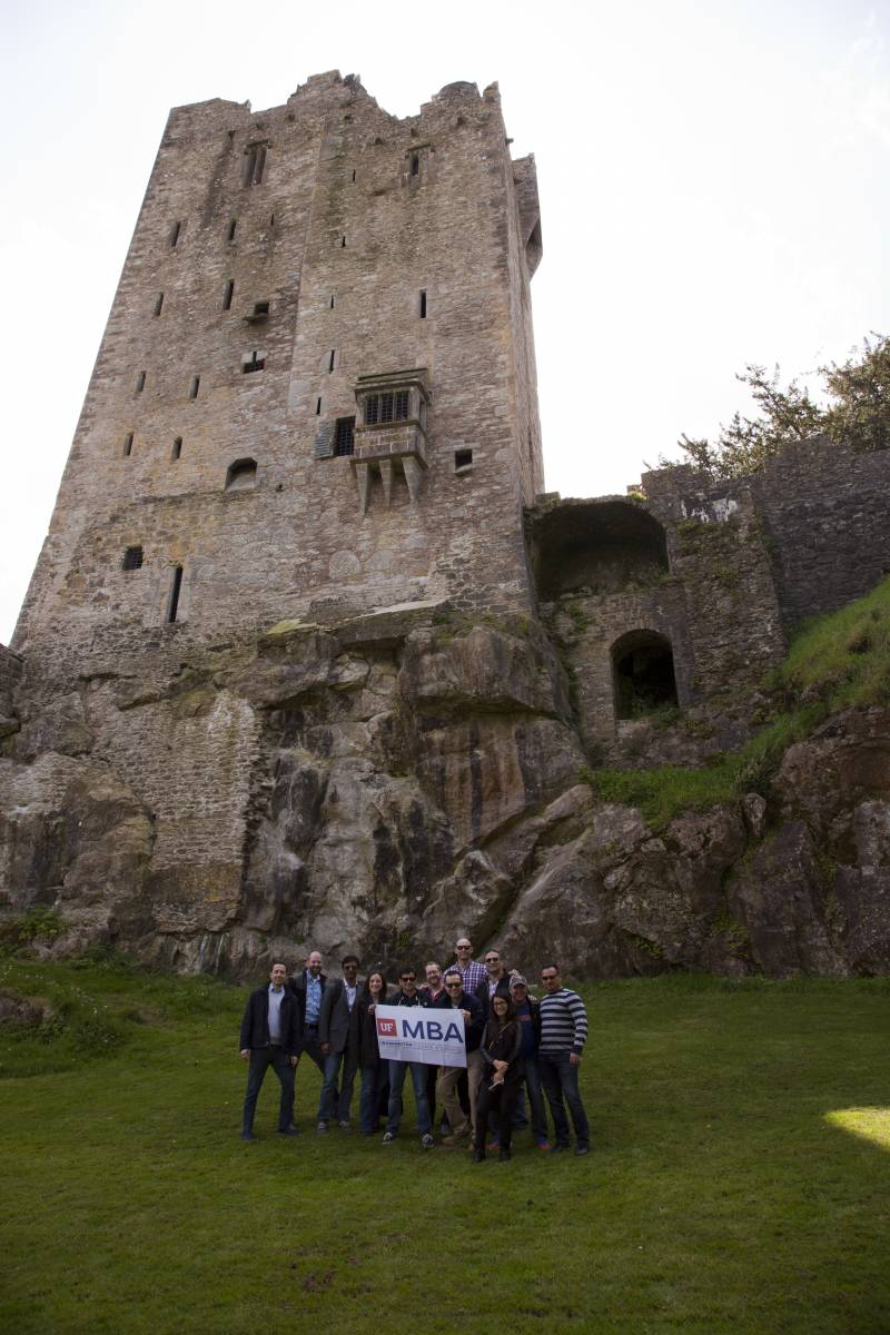 UF MBA students on the Global Immersion Experience in Dublin, Ireland hold a UF MBA banner with a castle in the background