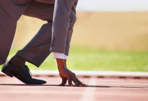 View of a man in a track starting position wearing a business suit