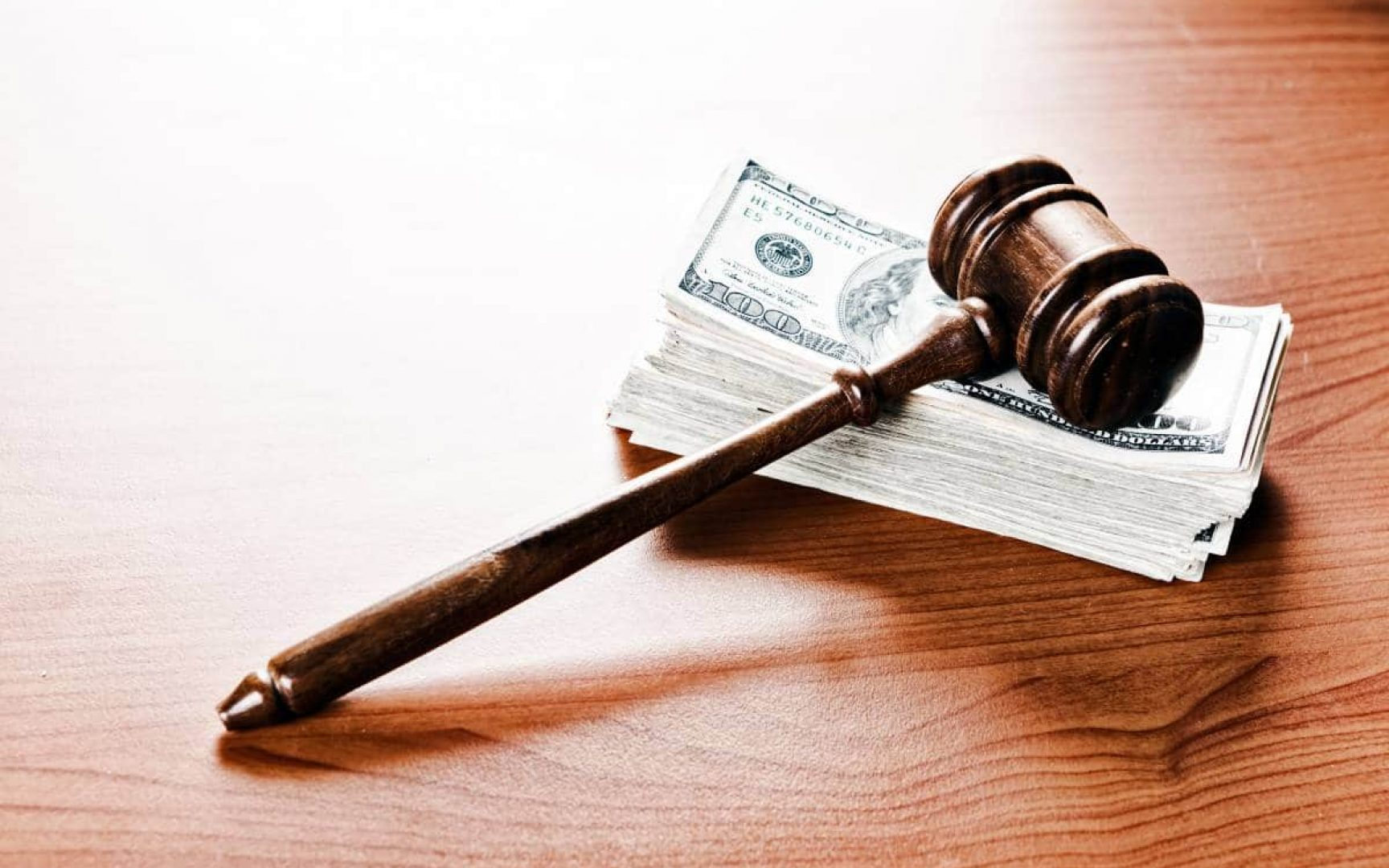 Gavel sitting on top of a large stack of money