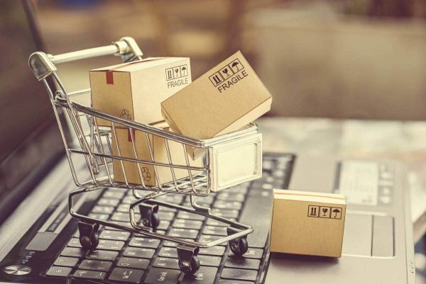 Small shopping cart sitting on a laptop with shipping boxes inside the cart.