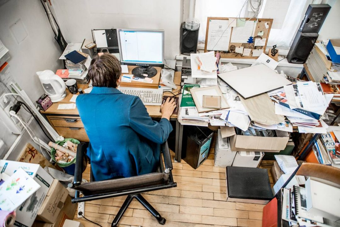 High Angle View Of Office Worker Working On Computer with a cluttered desk