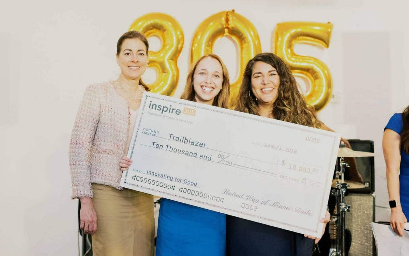 Lauren Koff holds a large check with her business partner and administrator
