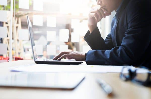 Man looking at a laptop screen while thinking