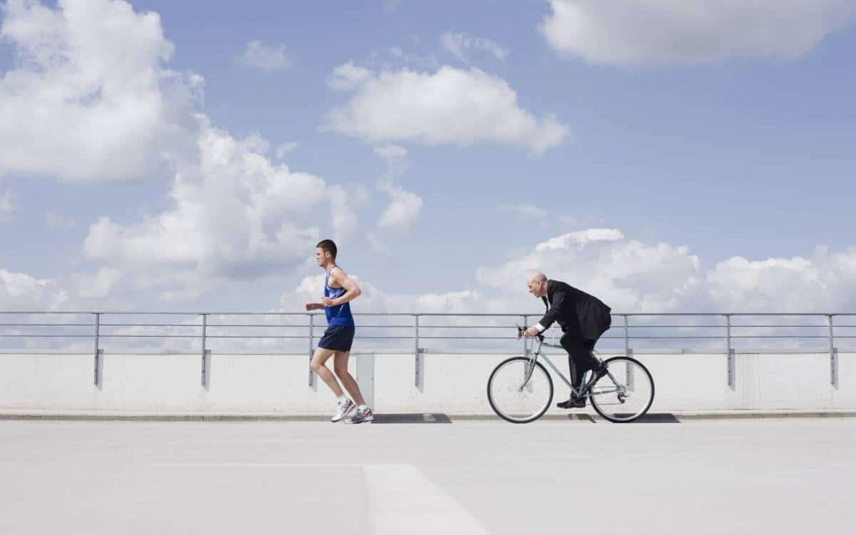 Man running followed by a man on a bike