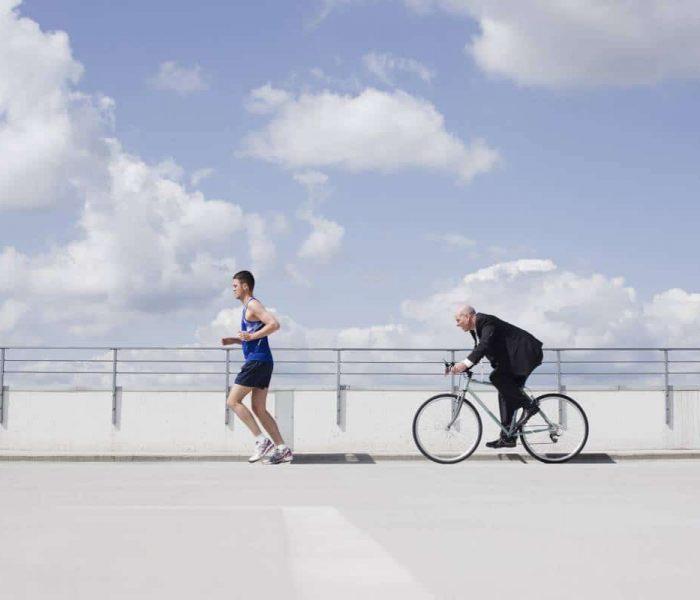 Man running followed by a man on a bike