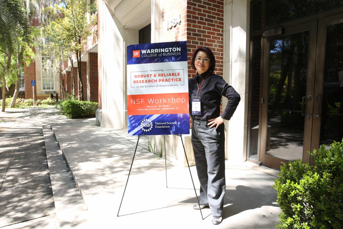 Gwen Lee with the Robust and Reliable Research Practice Seminar sign