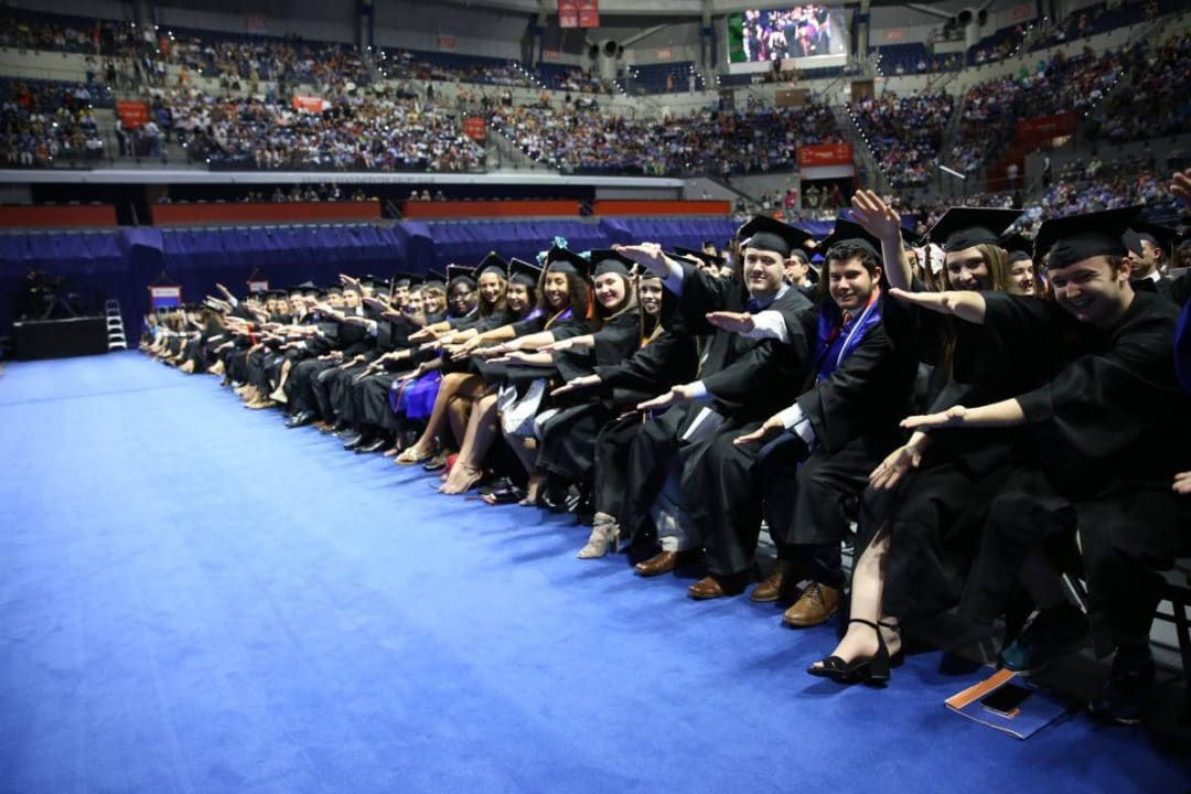 Students in graduation regalia doing the Gator chomp in the O'Connell Center at the UF Commencement ceremony