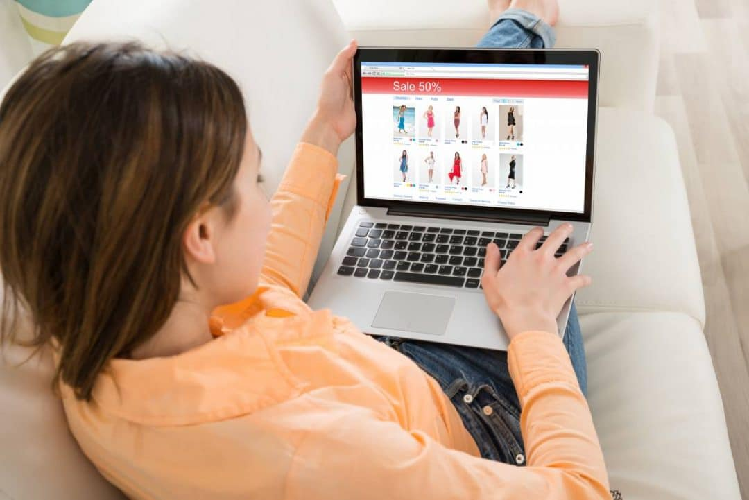 Woman sitting on couch online shopping on a laptop