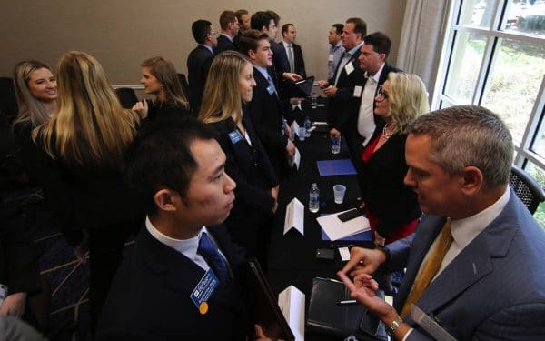 Students in suits talking with company recruiters