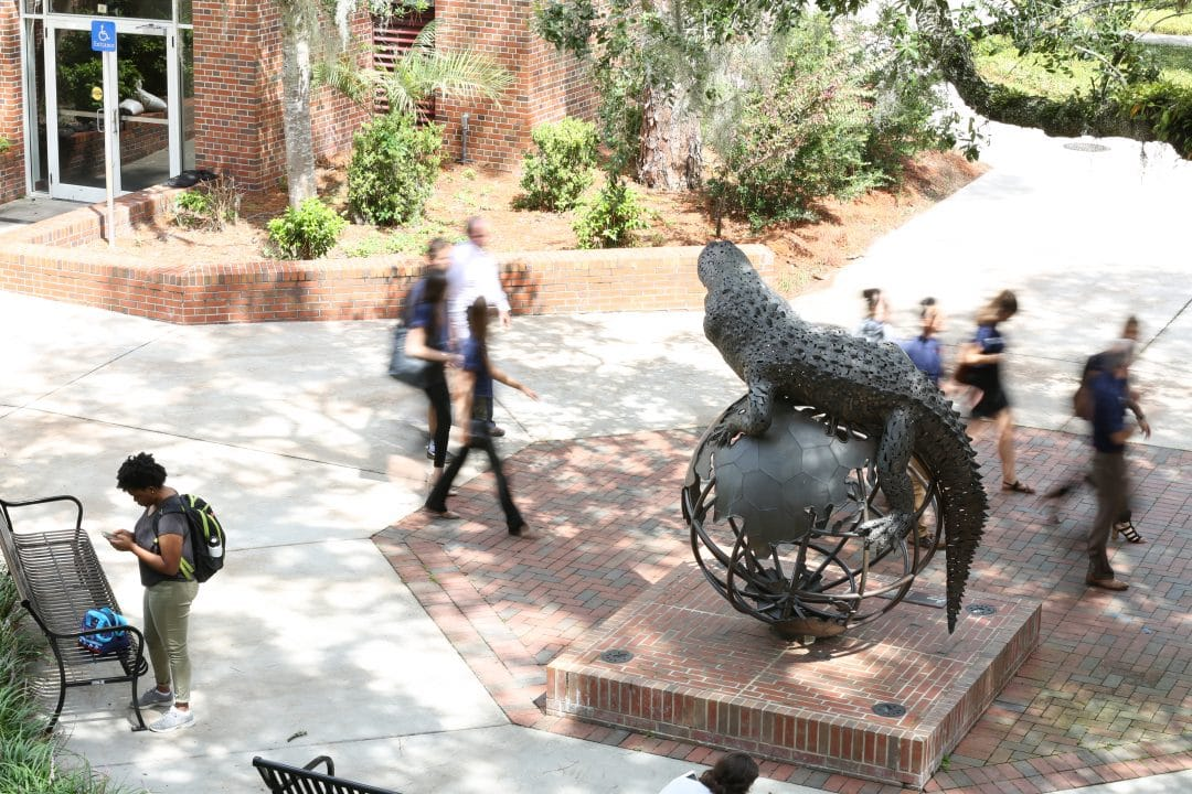 Gator Ubiquity Statue with people in motion around the statue.
