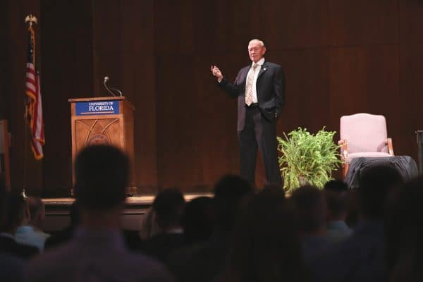 General Martin Dempsey stands on stage next to a podium that reads University of Florida in front of a large group of students