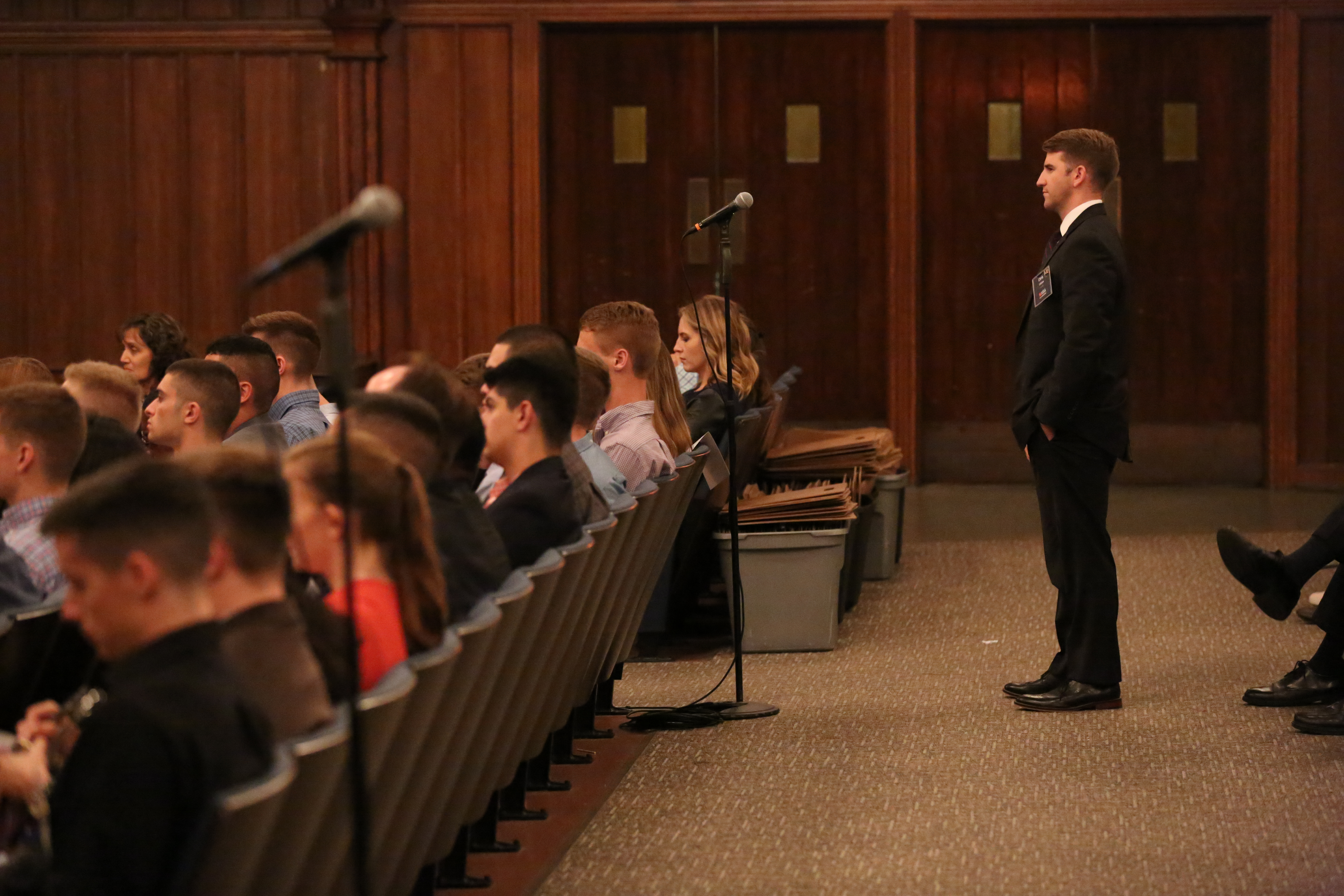 Student standing in front of a microphone to ask a question of General Dempsey in the University Auditorium.