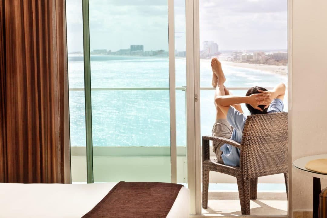Man on vacation, sunbathing and enjoying the view of the Caribbean Sea from the room balcony of a resort hotel in Cancun, Riviera Maya, Mexico.